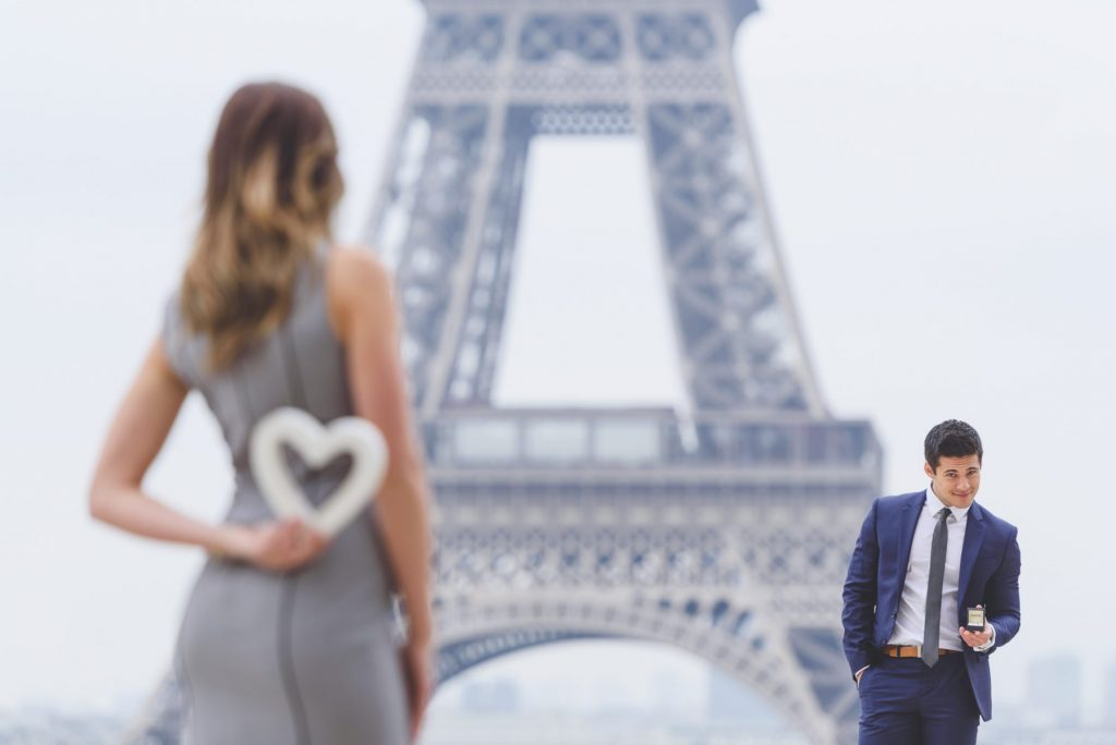 Paris photographer Paris engagement photos at the Eiffel Tower with cool prop
