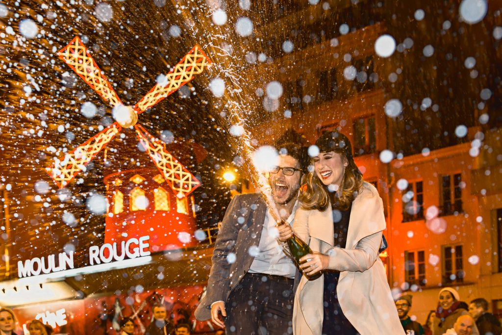 Paris engagement session at Moulin Rouge with Champagne popping as prop